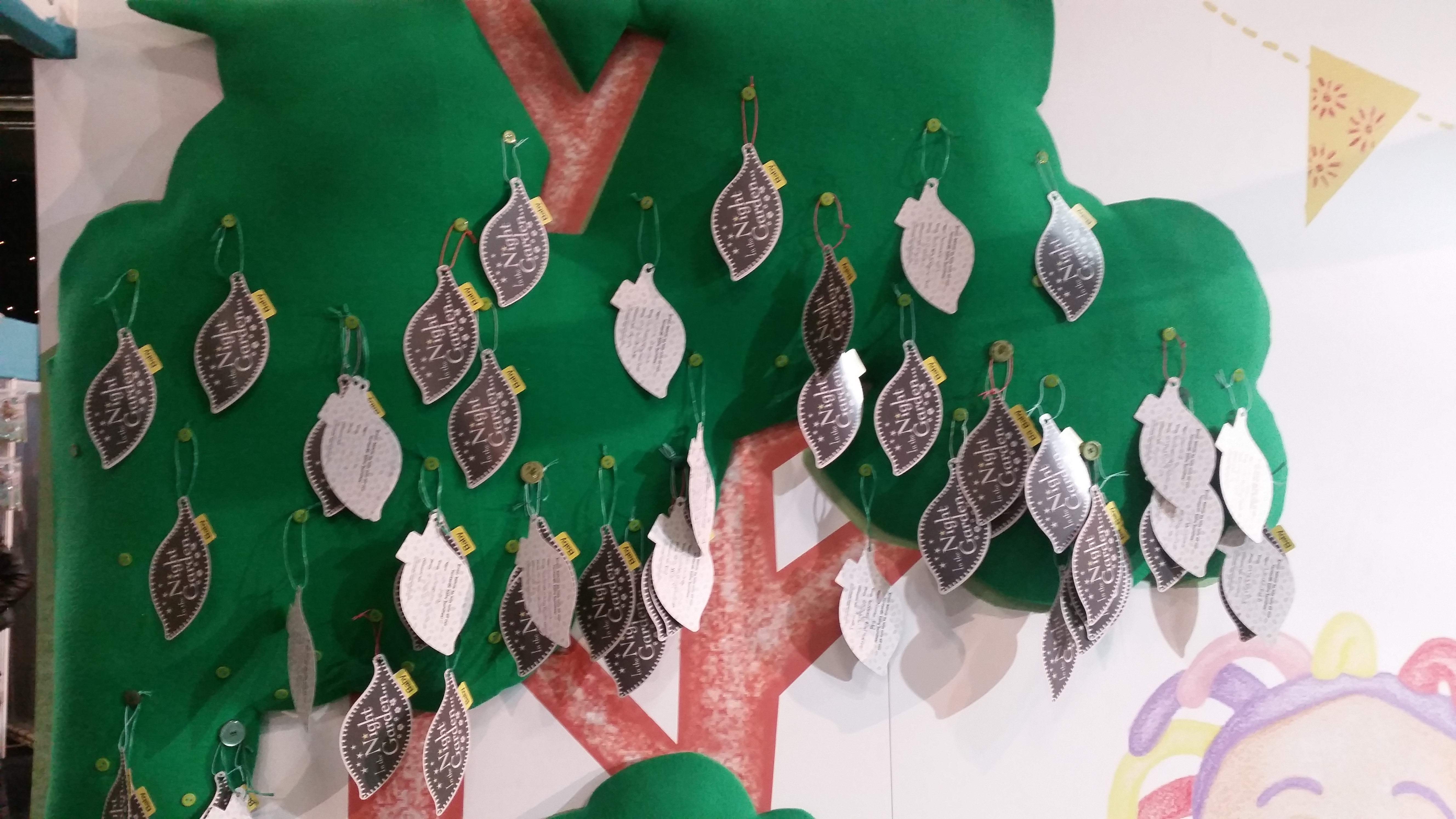Silver In The Night Garden branded leaves hang from a green tree on a wall