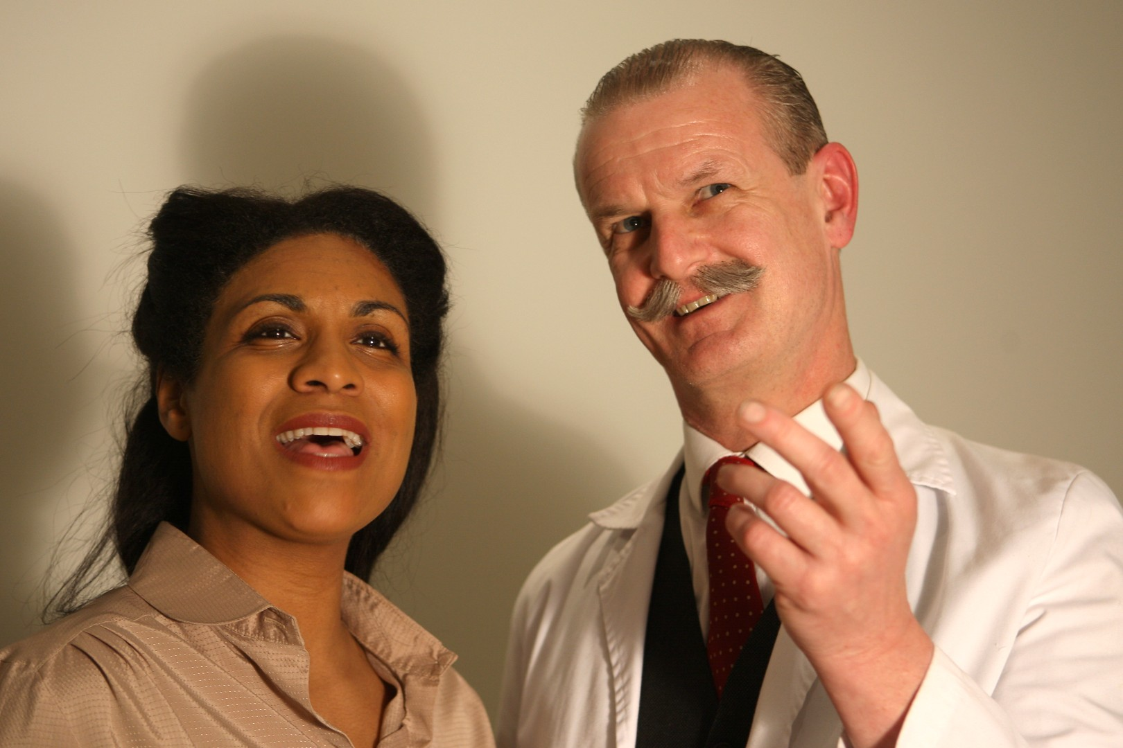 A mixed race lady in beige chemise and mustachioed biologist in labcoat pose emphatically together