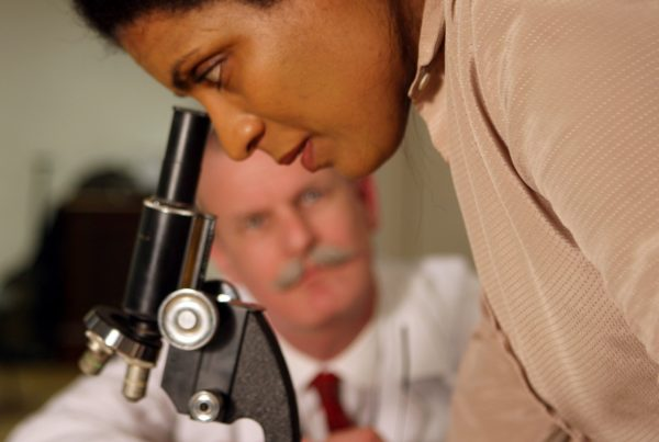 A woman looks into a microscope as a mustachioed biologist watches on in soft focus