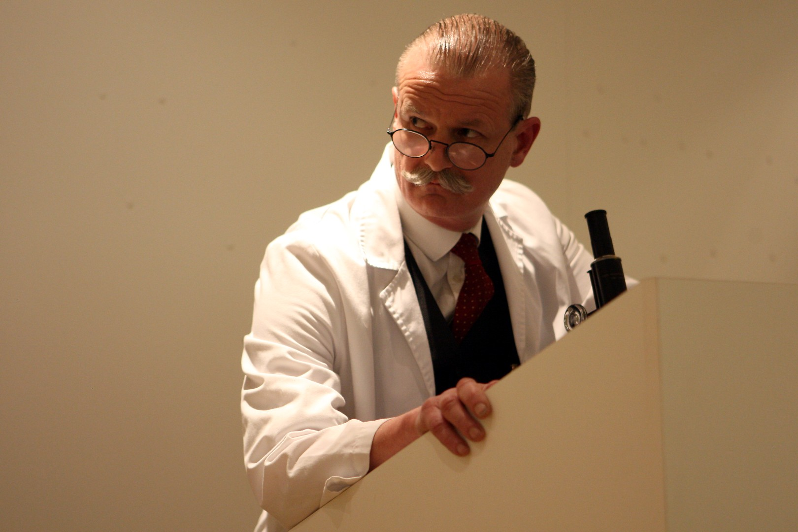 A mustachioed biologist in a white lab coat looking concerned.