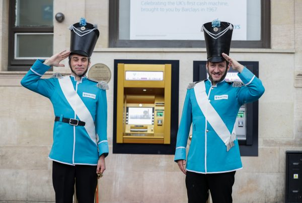 2 guards salute dressed in Barclays brand colour cyan stand either side of a golden ATM at the celebration of the world's first ATM