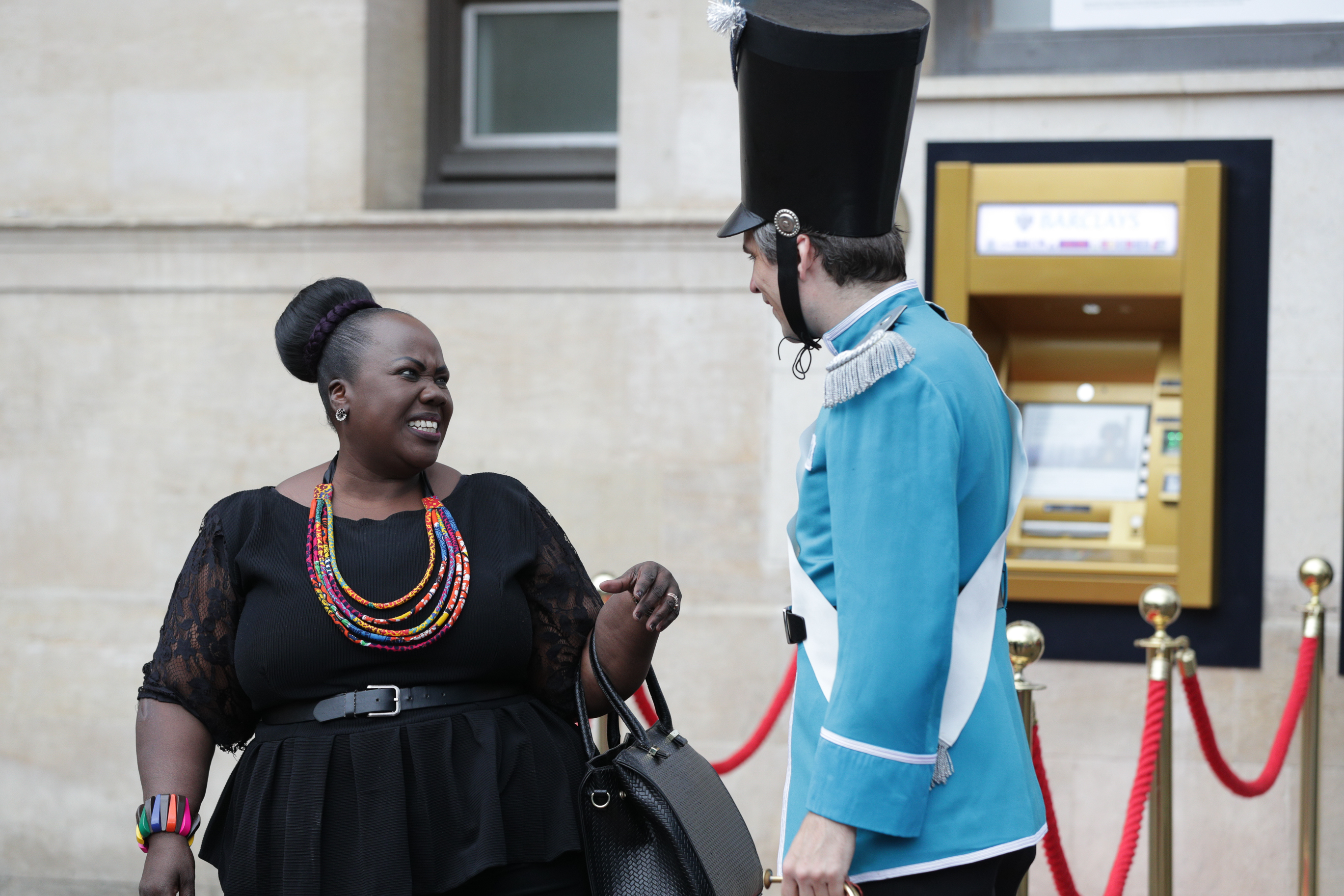 A guard dressed in Barclays brand colour cyan talks to a smiling woman in front of a gold ATM at the celebration of the world's first ATM