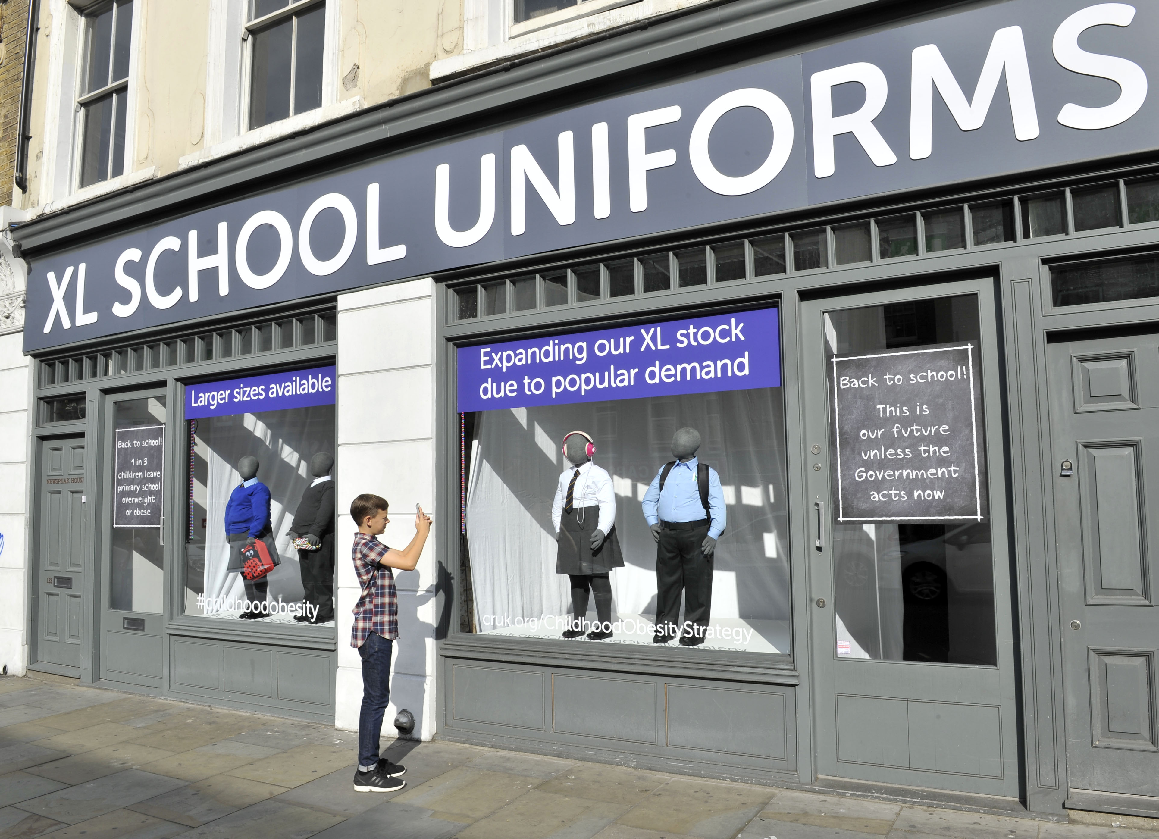 A young boy in a checked shirt takes a photo of a window display containing obese mannequins in tight school uniforms.