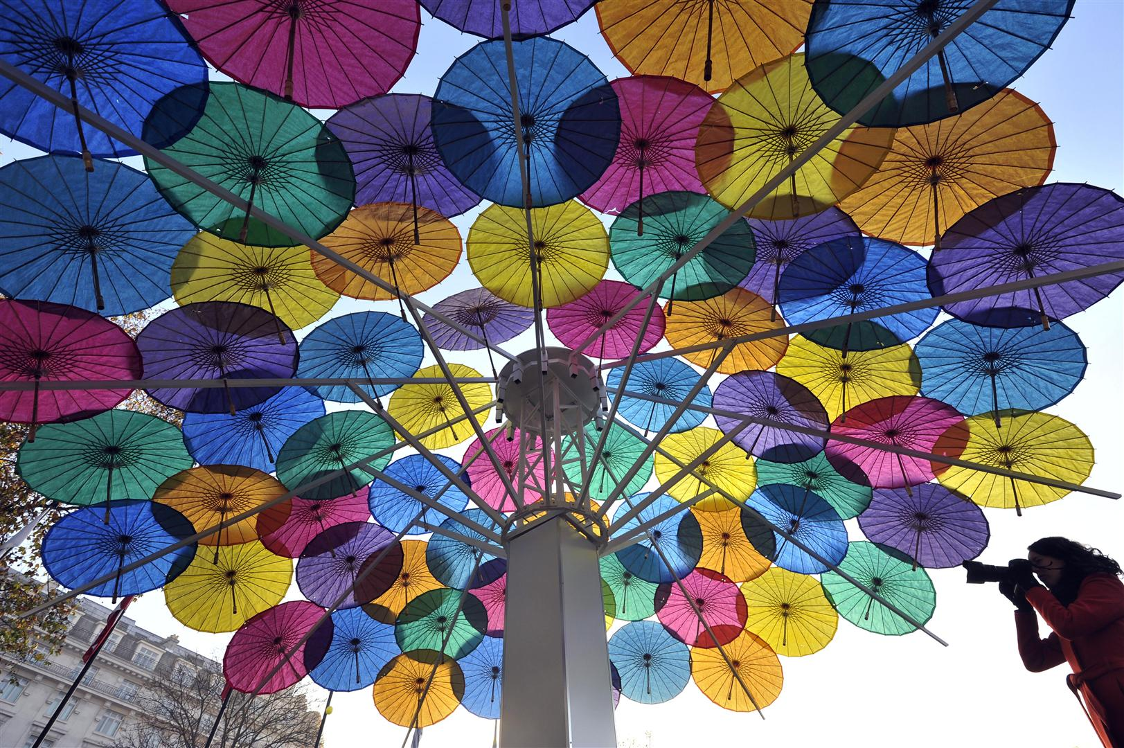 A lady in a red coat takes a photo underneath a giant cocktail umbrella constructed lots of multi-coloured parasols.