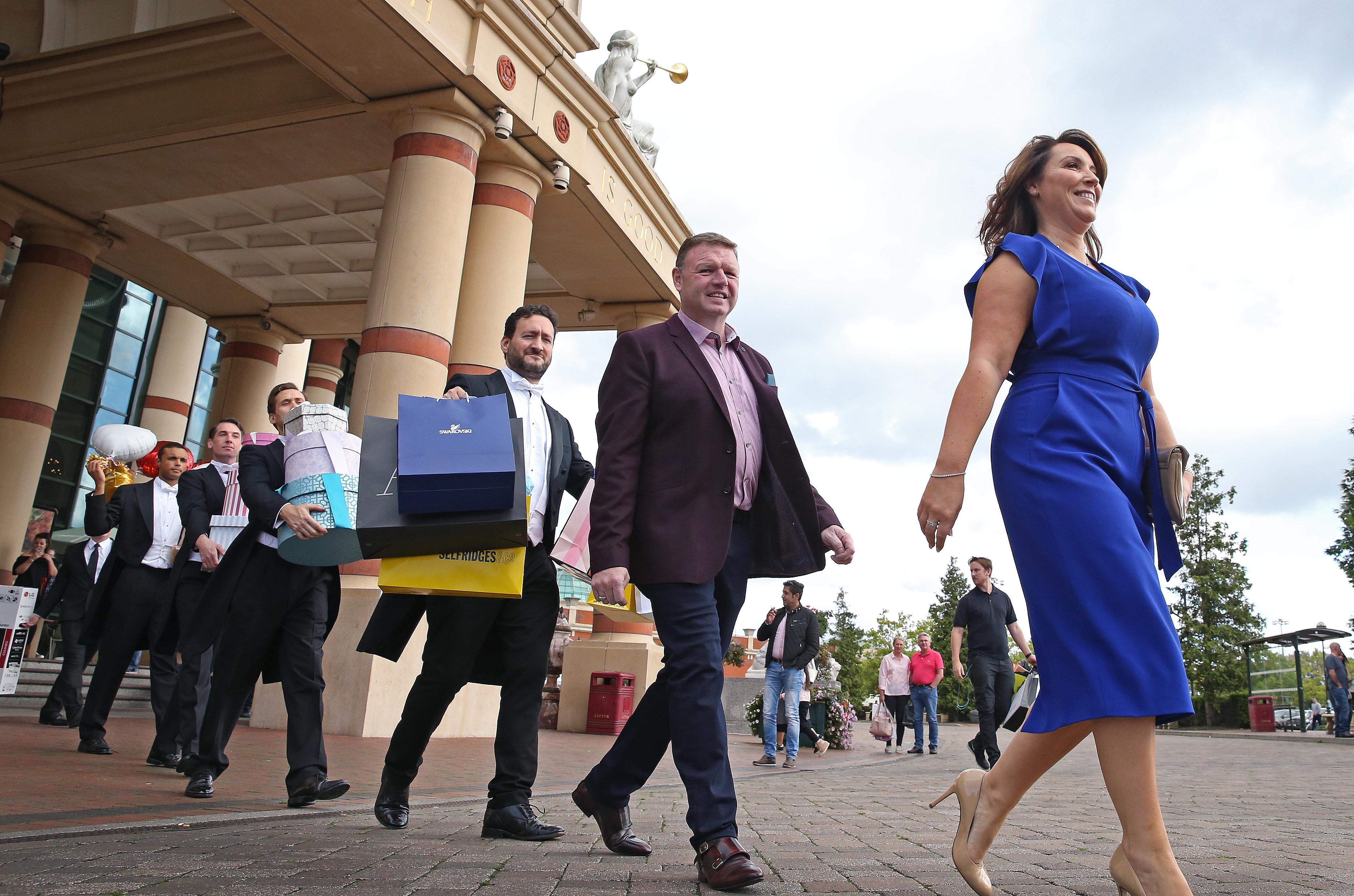 A line of very smart butlers and security guards in black and white suits, follow a smiling couple out of a shopping centre carrying colourful shopping bags and boxes.