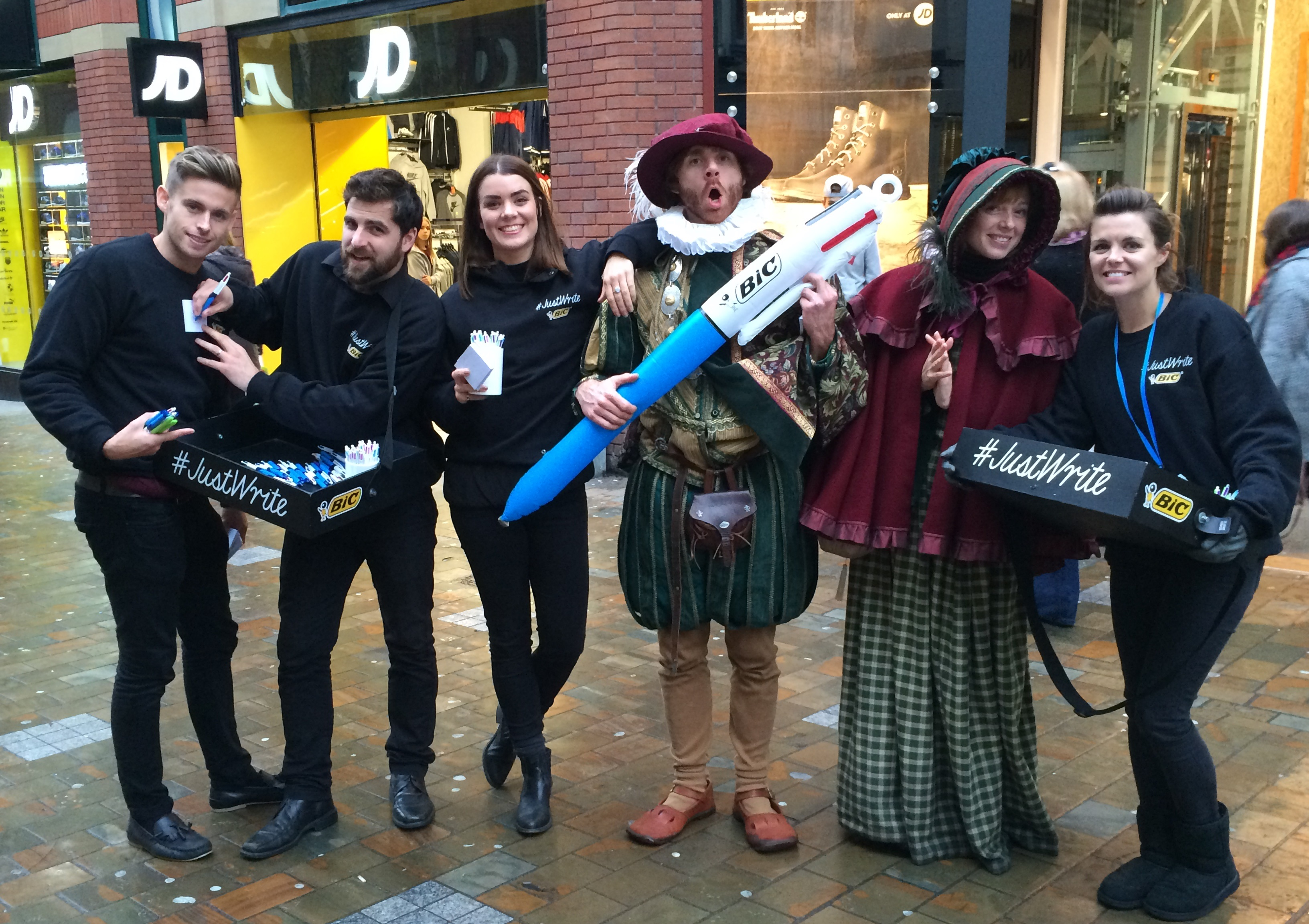 A group of promotional performers stand in a line alongside actors dressed as Emily Bronte and William Shakespeare, who holds a giant pen.