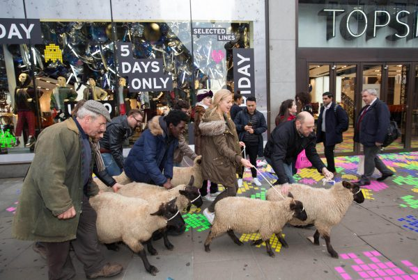 A group of people dressed as shoppers each holding a woolly sheep on a rope stand outside the entrance of Topshop on London's Oxford St, as passersby in business suits watch on perplexed.