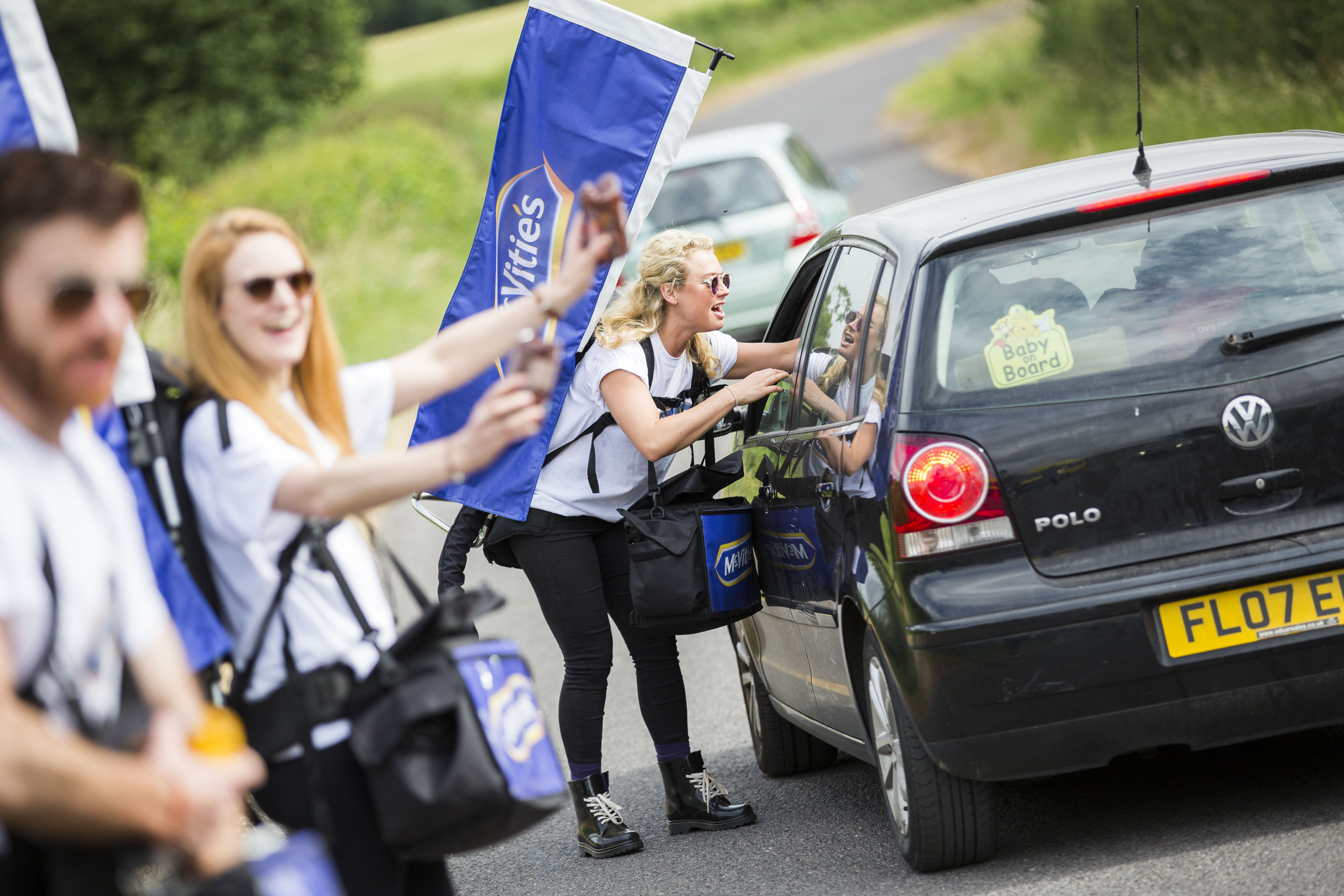 A pretty female performer is smiling as she leans into a car, pouring a cup of tea, as the car leaves Glastonbury festival