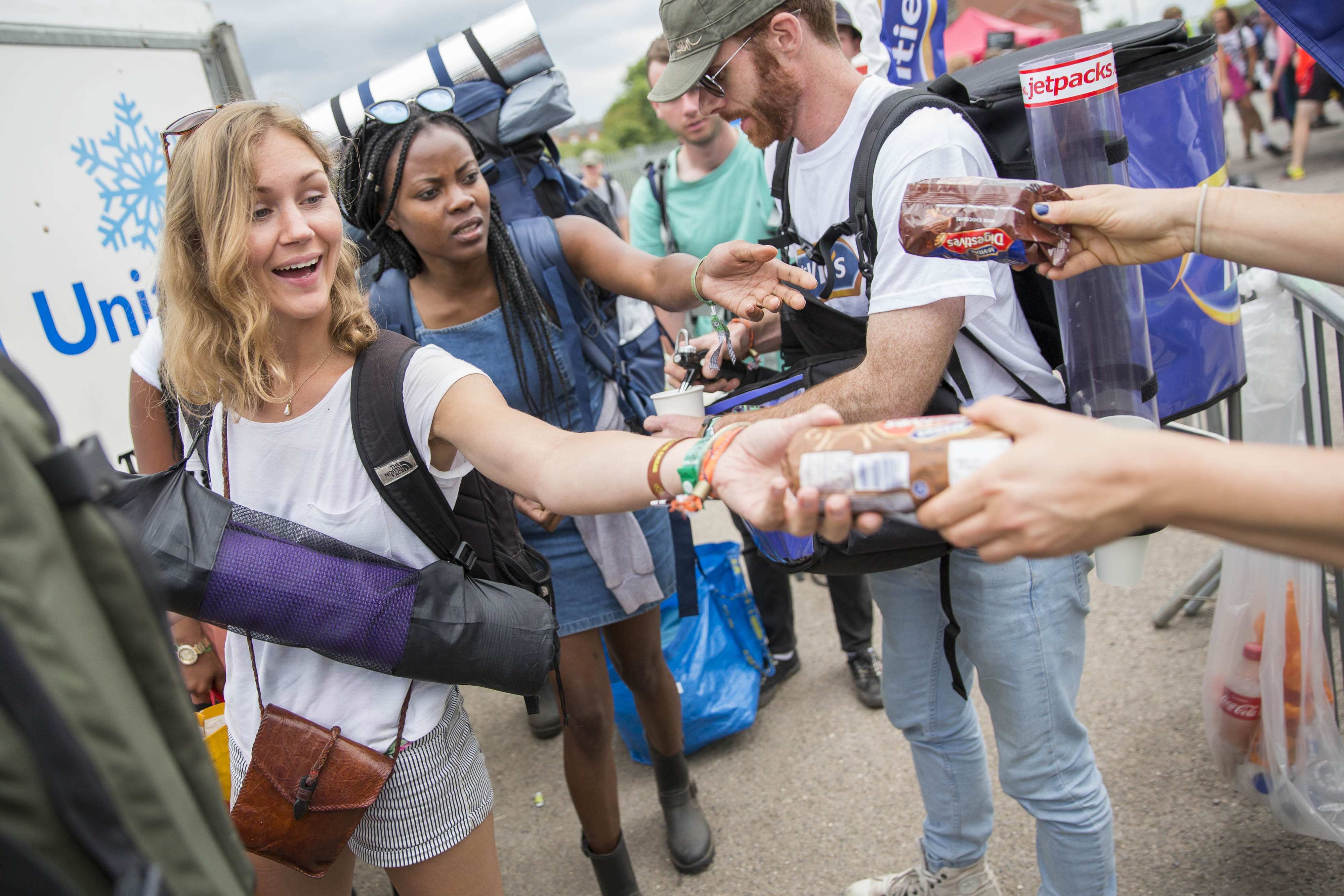 A queue of festival goers leaving Glastonbury excited as they are handed packets of McVities biscuits and cups of tea.