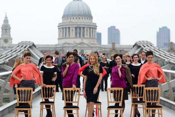 A group of dancers in colourful clothing stand with TOWIE star Lydia Bright in front of St Paul's cathedral
