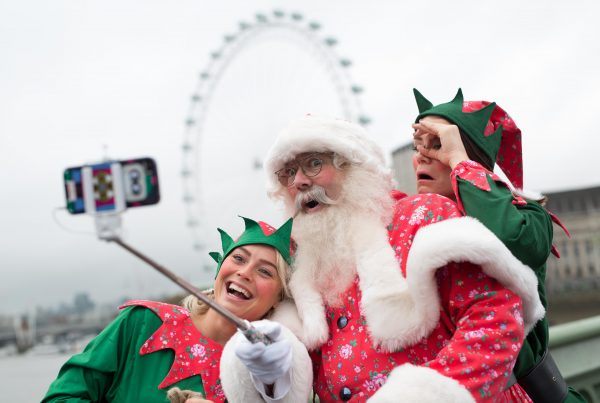 A white-bearded Father Christmas in a traditional bright red Father Christmas outfit with added Cath Kidston Bramley Sprig patterning, and his two rosy cheeked red and green elves use a selfie stick to photograph themselves on Westminster Bridge.The elves and father christmas are happy and excited, and thr London eye is framed in the background of the shot.
