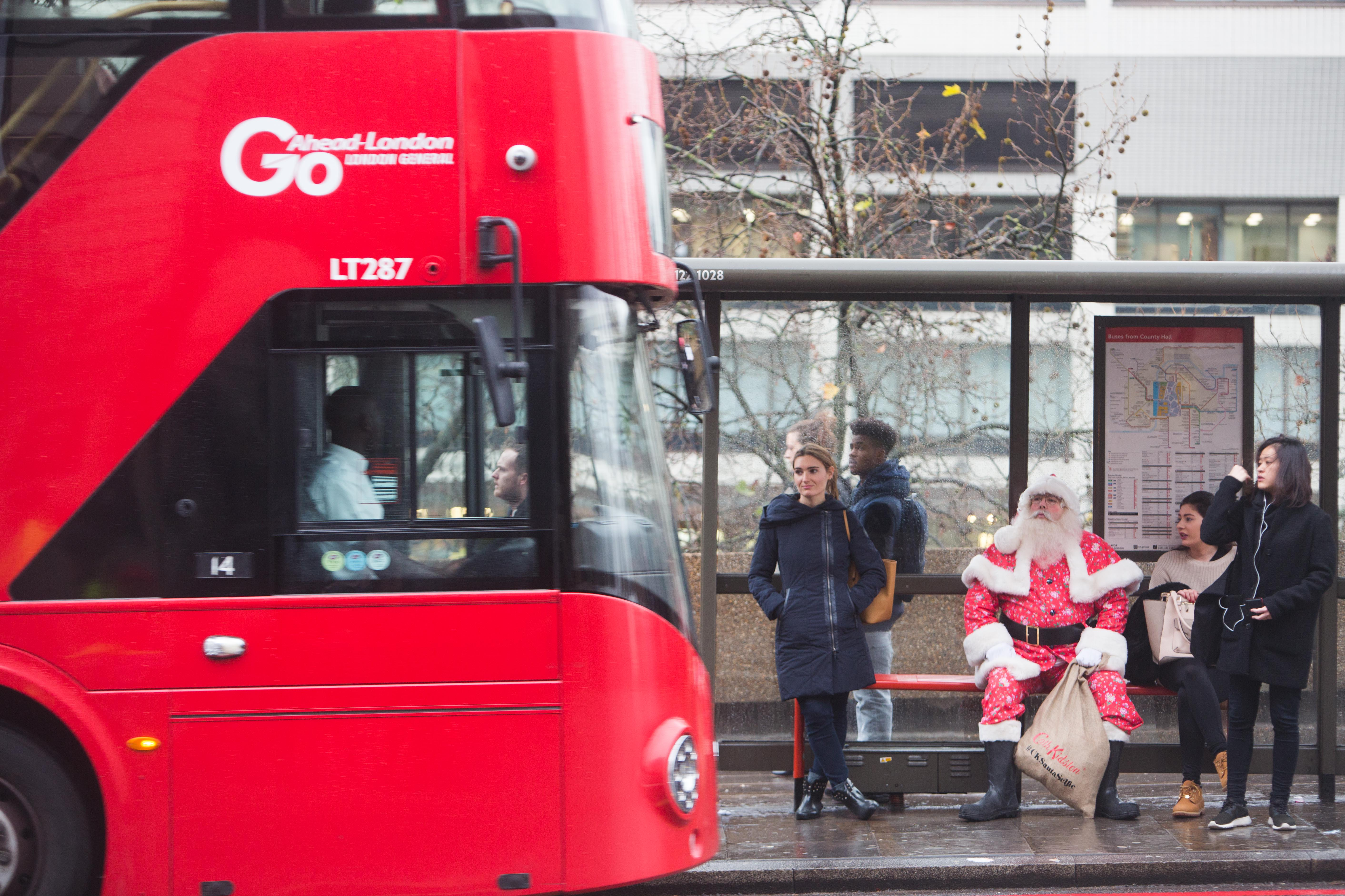 A white-bearded Father Christmas in a traditional bright red Father Christmas outfit with added Cath Kidston Bramley Sprig patterning, sits at a bustop alongside regular members of the public, pretending to await the arrival of a big red London bus, that is just pulling in.
