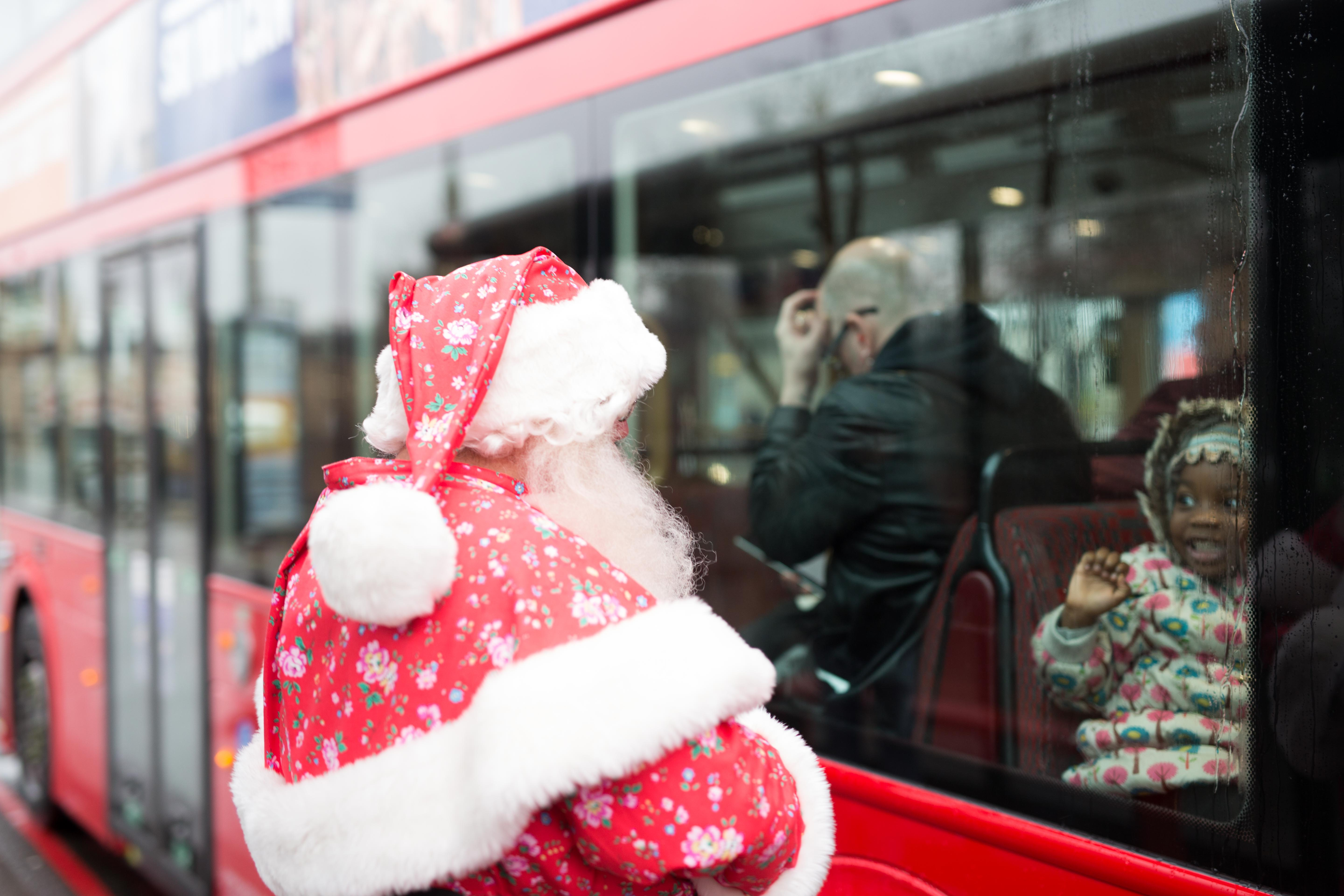 A white-bearded Father Christmas in a traditional bright red Father Christmas outfit with added Cath Kidston Bramley Sprig patterning, waves through the window of a red London bus, to an enchanted child in a flower-patterned anorak who waves back.