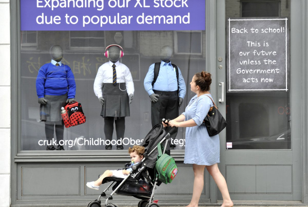 A mother pushing a child in a pushchair examines a window display containing obese mannequins in tight school uniforms.