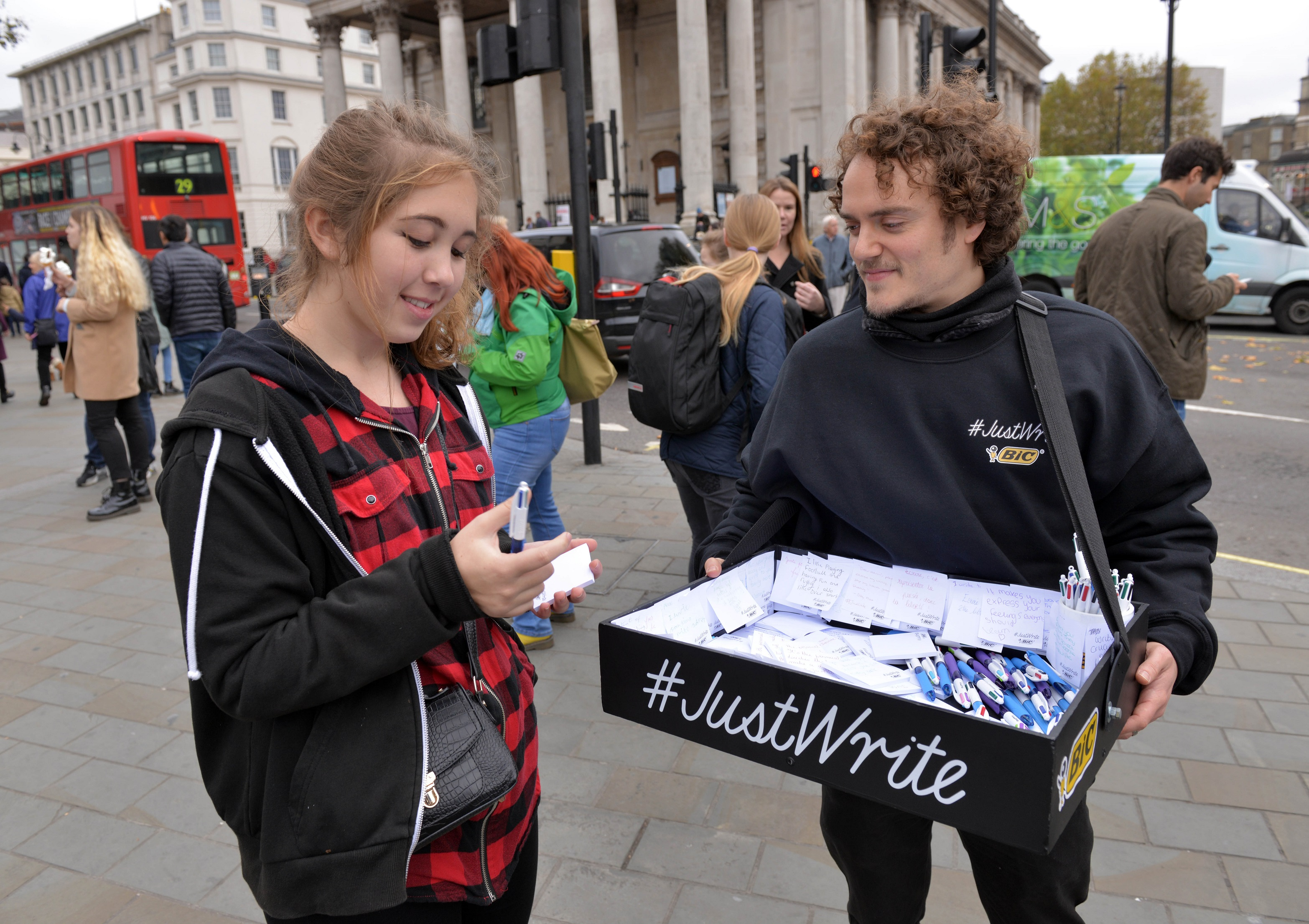A promotional team member with an usherette style writing tray, encourages a member of the public to write a hand-written note.