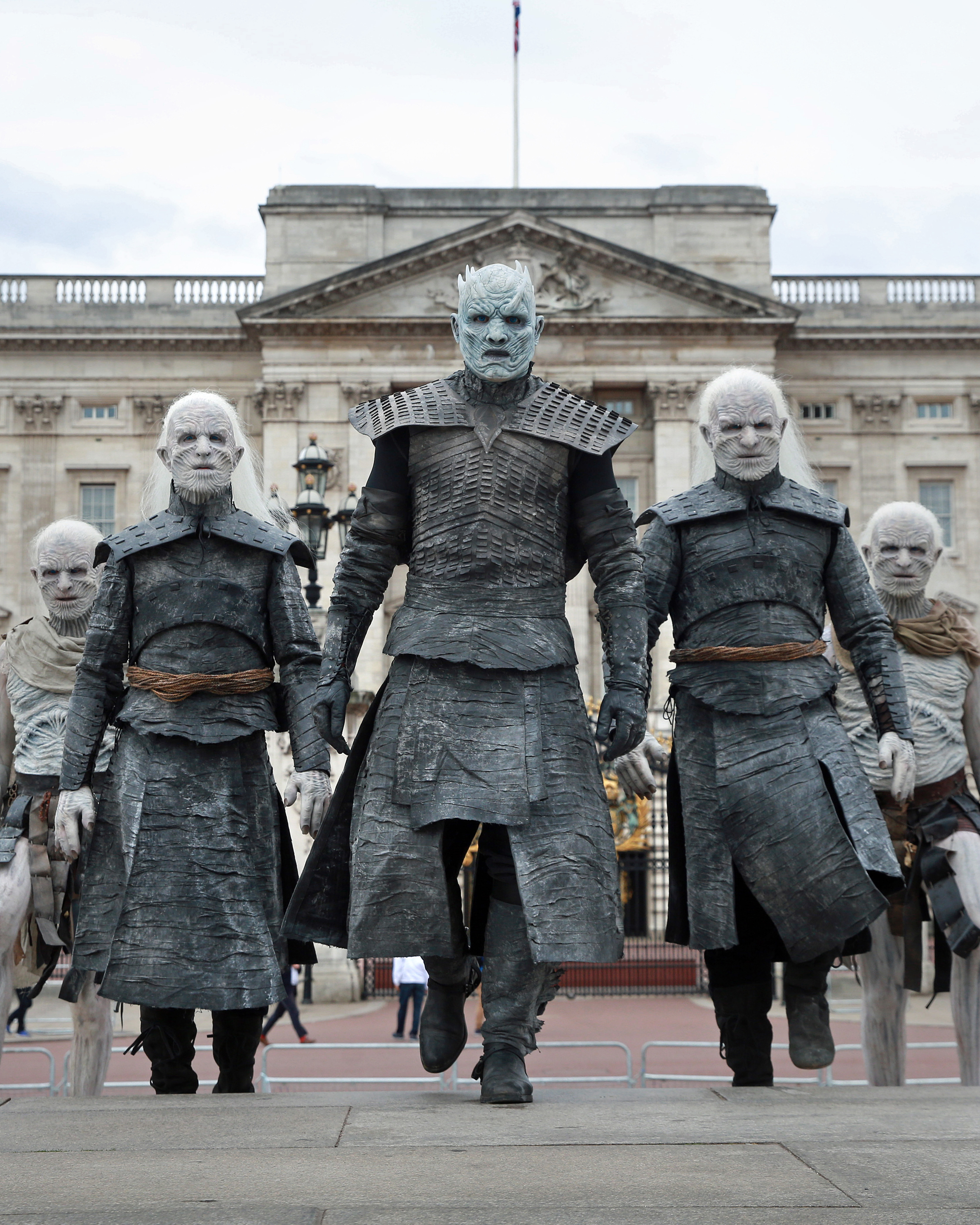 Five models dressed as 'White Walkers' from Game of Thrones, led by the 'Night King' on horseback, walk in front of Buckingham Palace in London