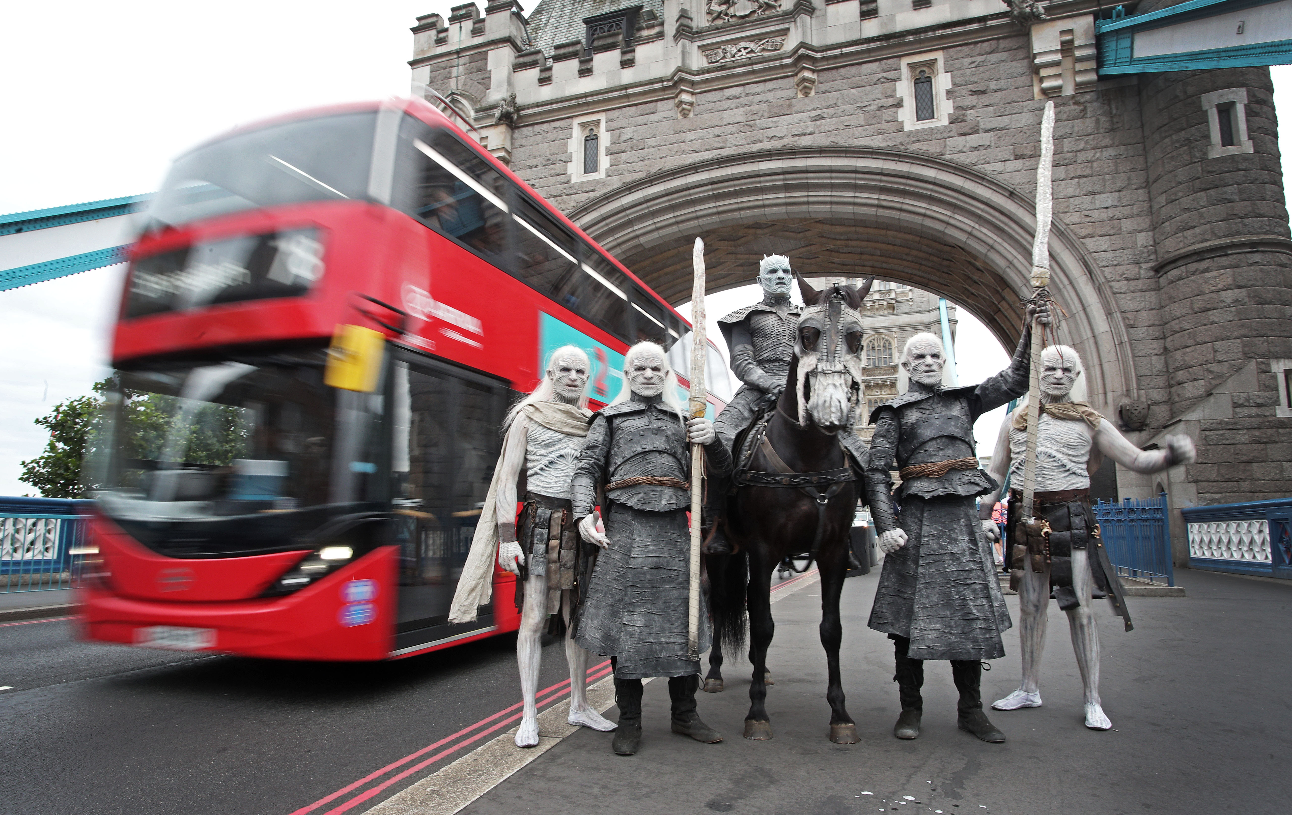 Five models dressed as 'White Walkers' from Game of Thrones, led by the 'Night King' on horseback, pass by The Tower of London in London