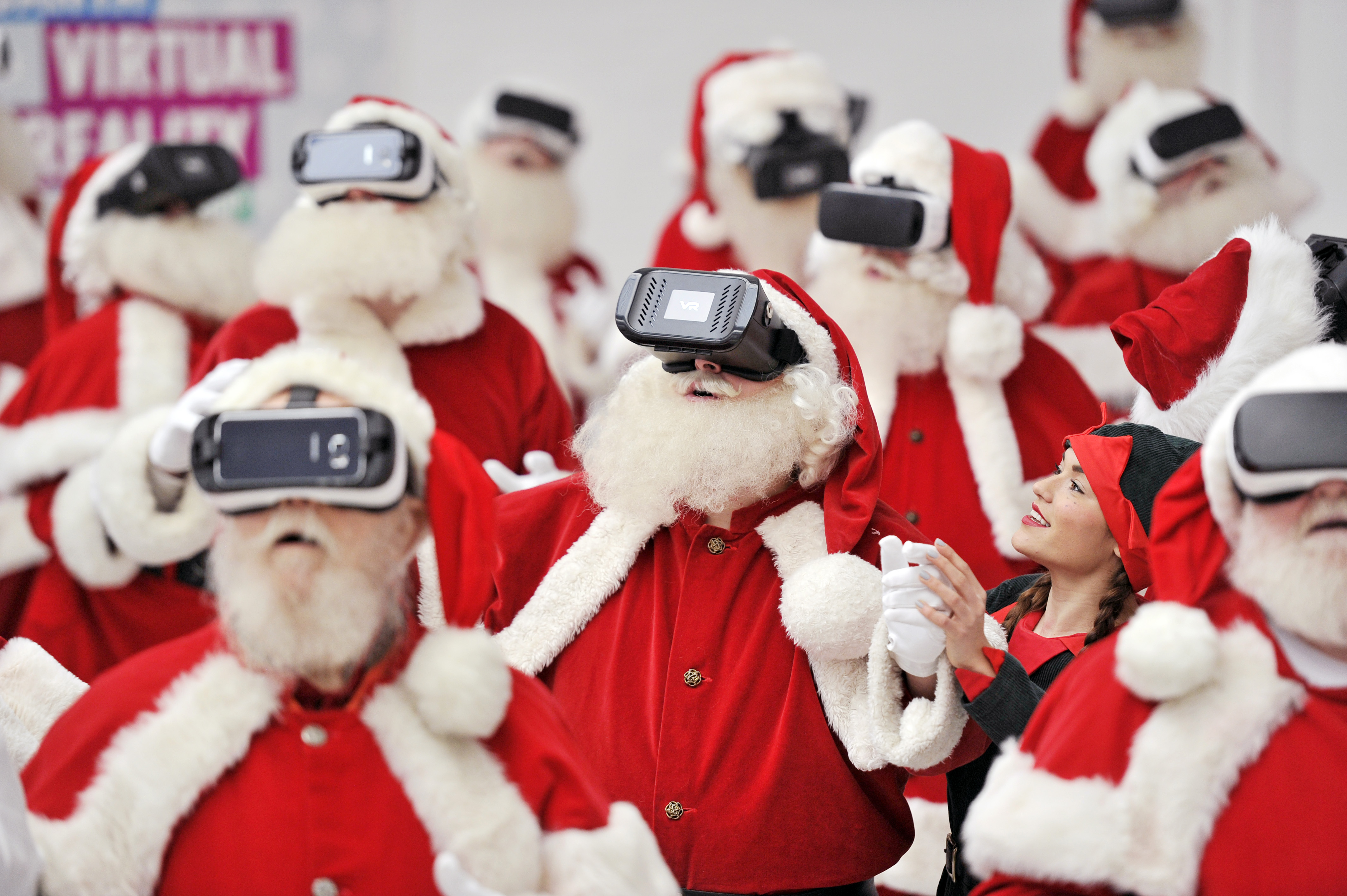 A group of Father Christmases wearing virtual reality headsets experience the technology being guided by an elf.