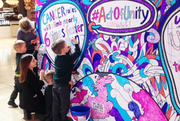 A group of adults and school children colour in a multicoloured mural for World Cancer Day in a shopping centre