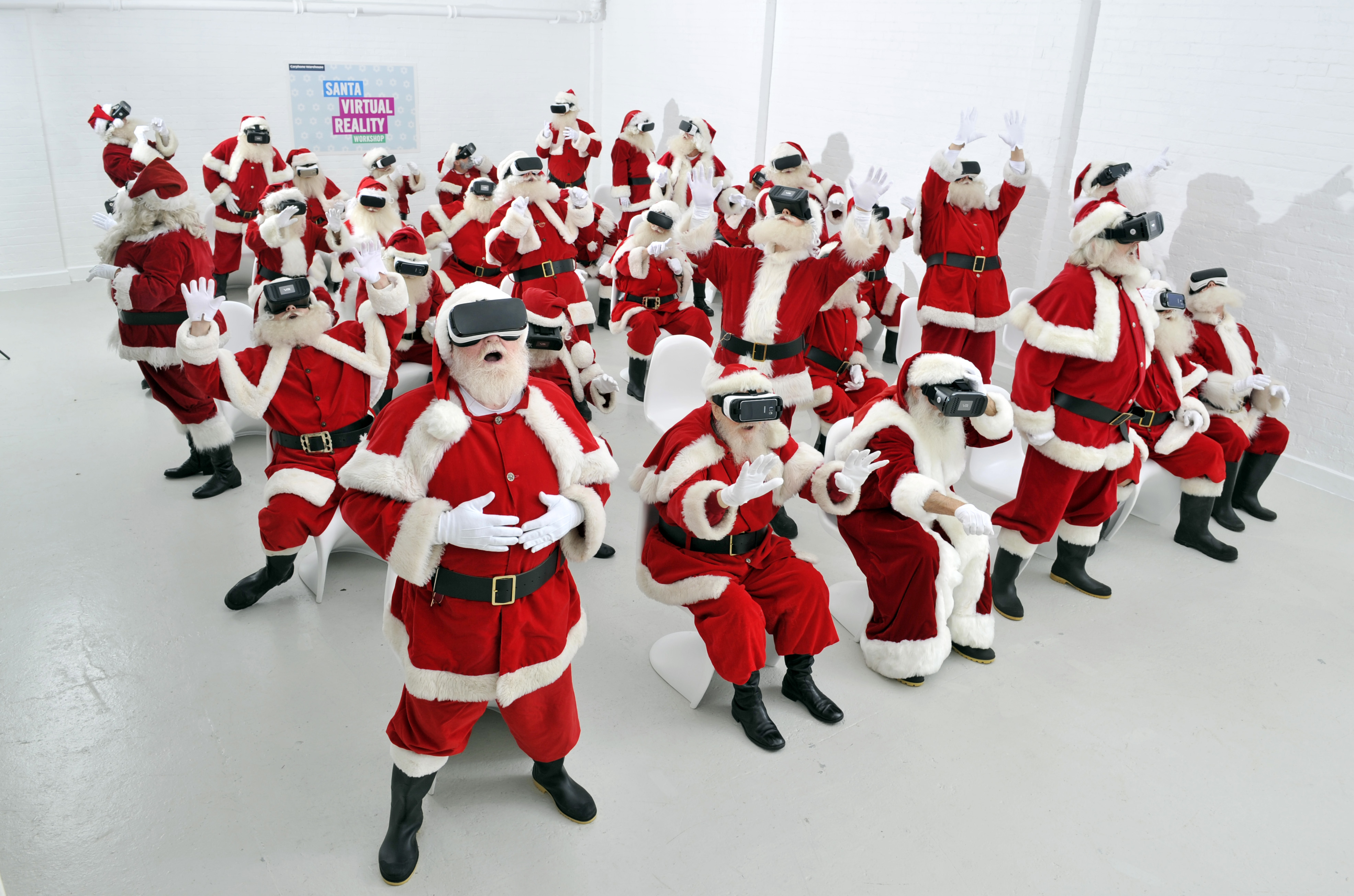 A group of Father Christmases wearing virtual reality headsets experience the technology.