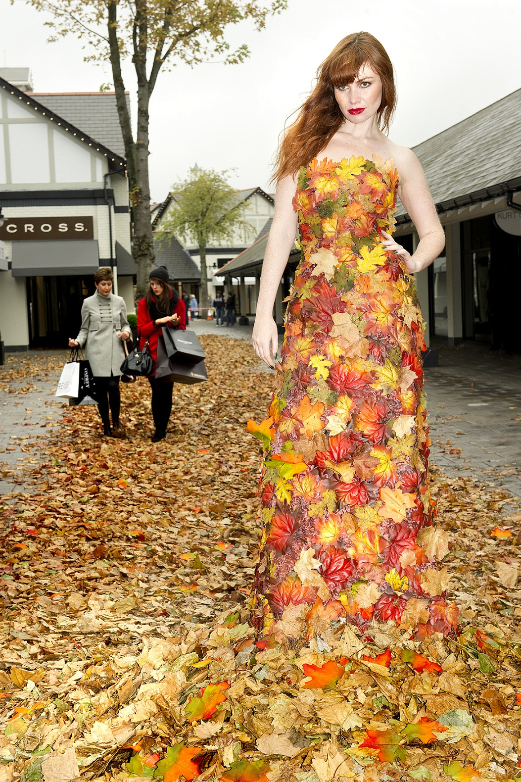 A mdoel wearing a dress made entirely out fo leaves poses as shoppers holding bags walk by