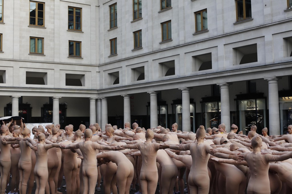 A group of 200 performers in flesh-coloured body-suits gather to form a giant hand