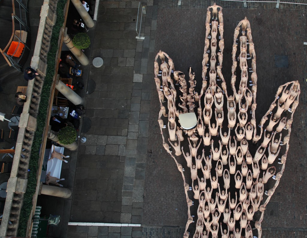 A group of 200 performers in flesh-coloured body-suits form the shape of a giant hand