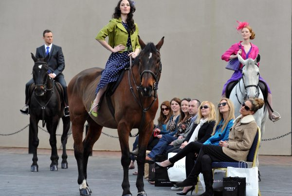 Models in designer clothes pose on horseback as members of the public watch on from a bench.