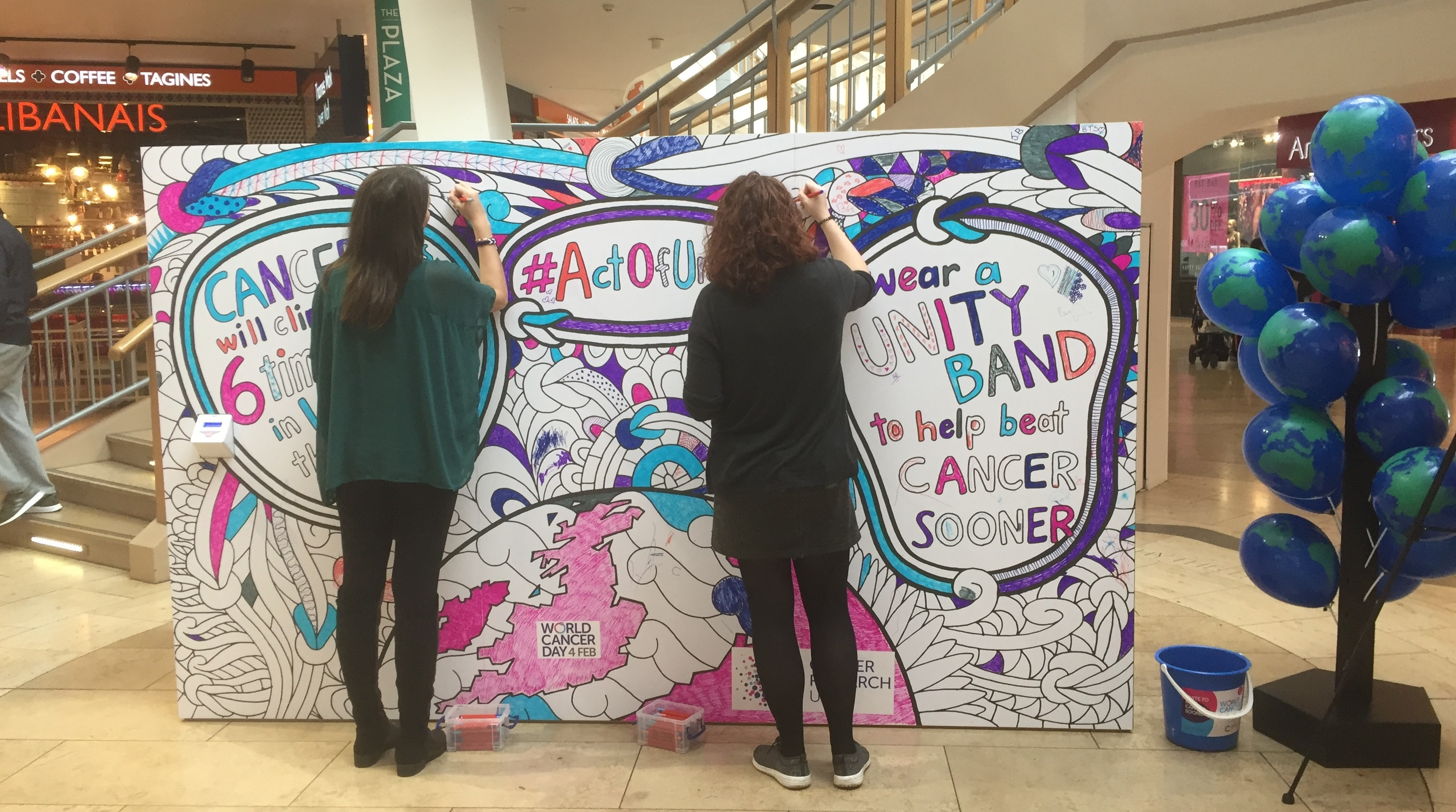 Two ladies colour in a multicoloured mural for World Cancer Day in a shopping centre