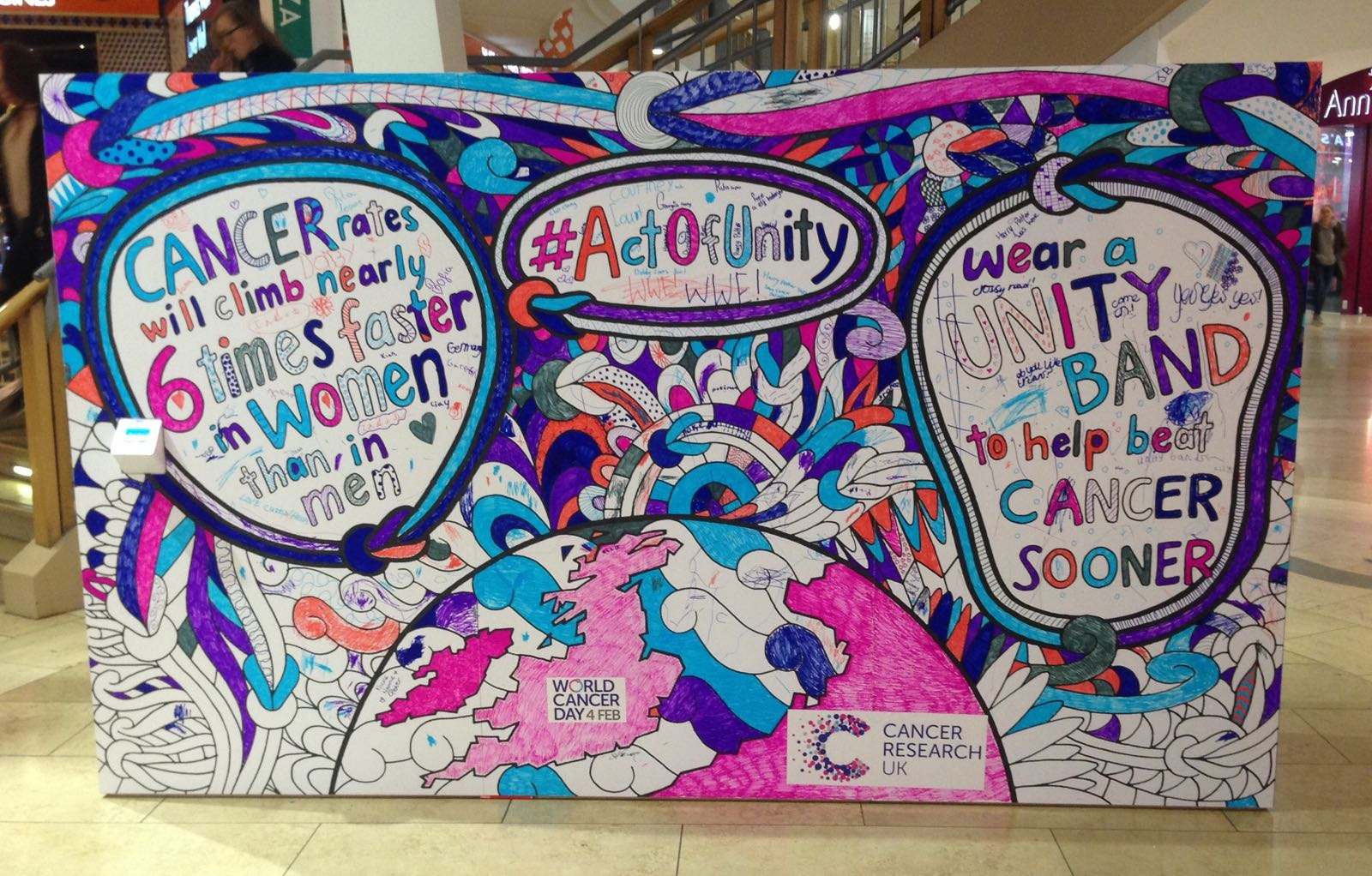 A multicoloured mural coloured in by the public for World Cancer Day in a shopping centre