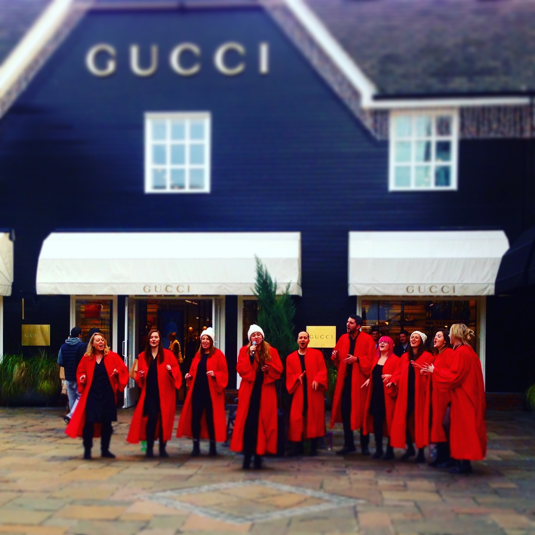 A ten-strong choir in red robes and white bobble hats sing in front of a Gucci shop