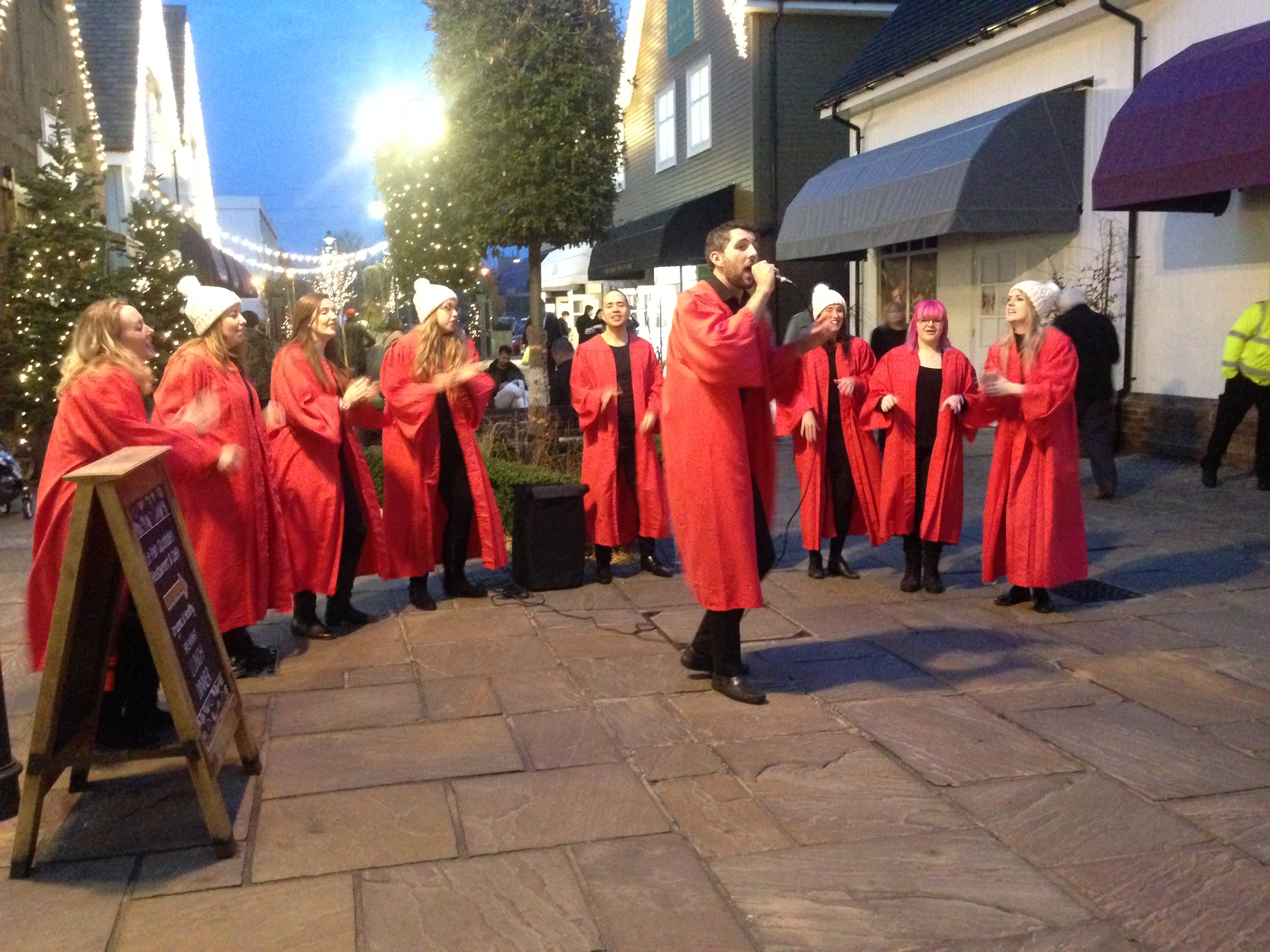 A ten-strong choir in red robes and white bobble hats sing in front of shops at Bicester village
