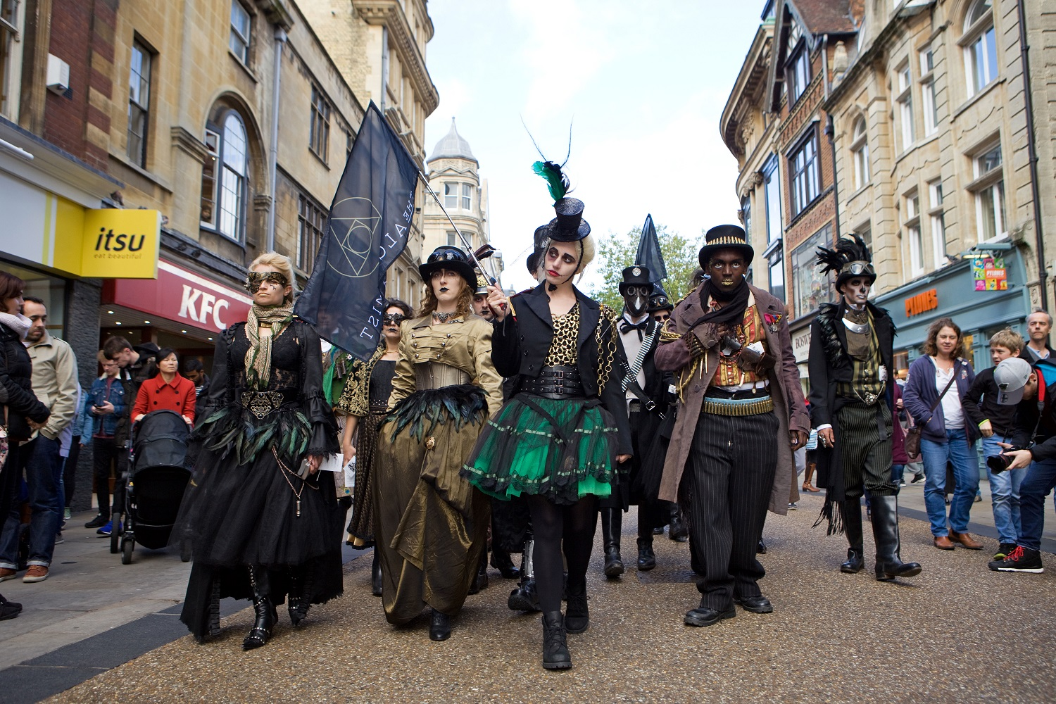 A group of attractive men and women strut along a street in Oxford, wearing Streampunk clothing
