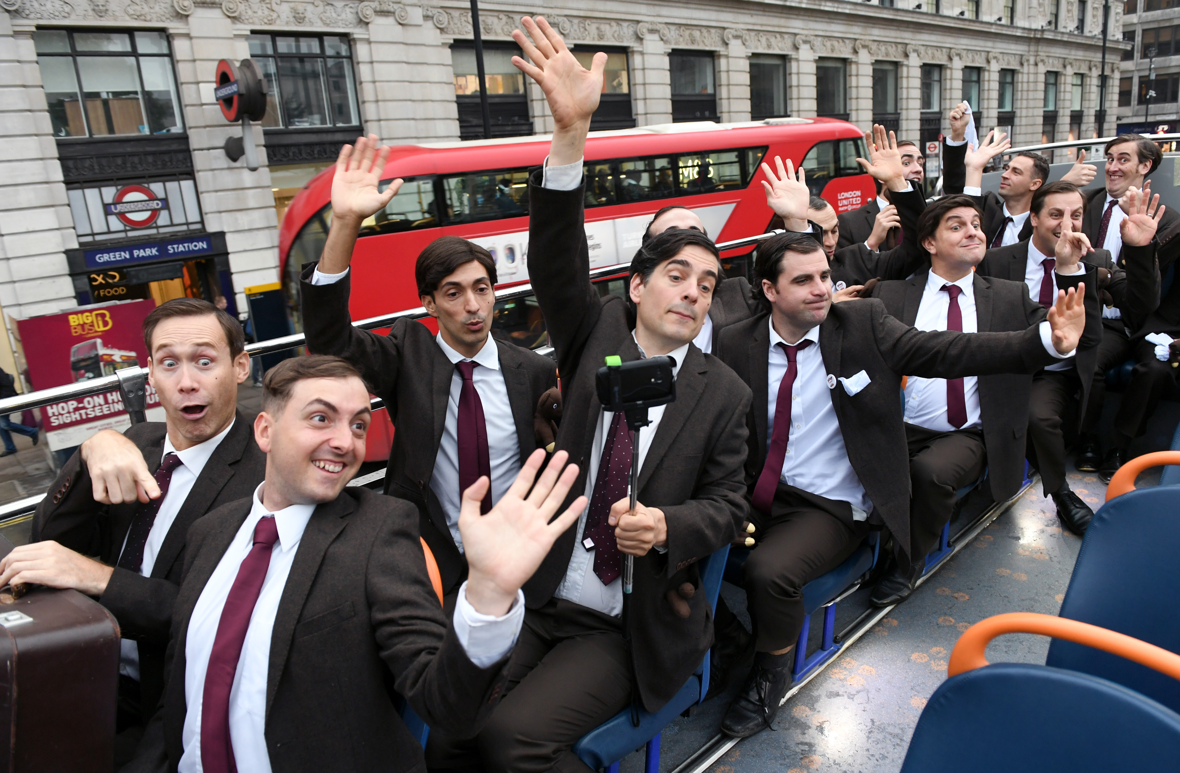 A group of men dressed as Mr Bean sit on the top deck of a bus touring London in front of a London Bus