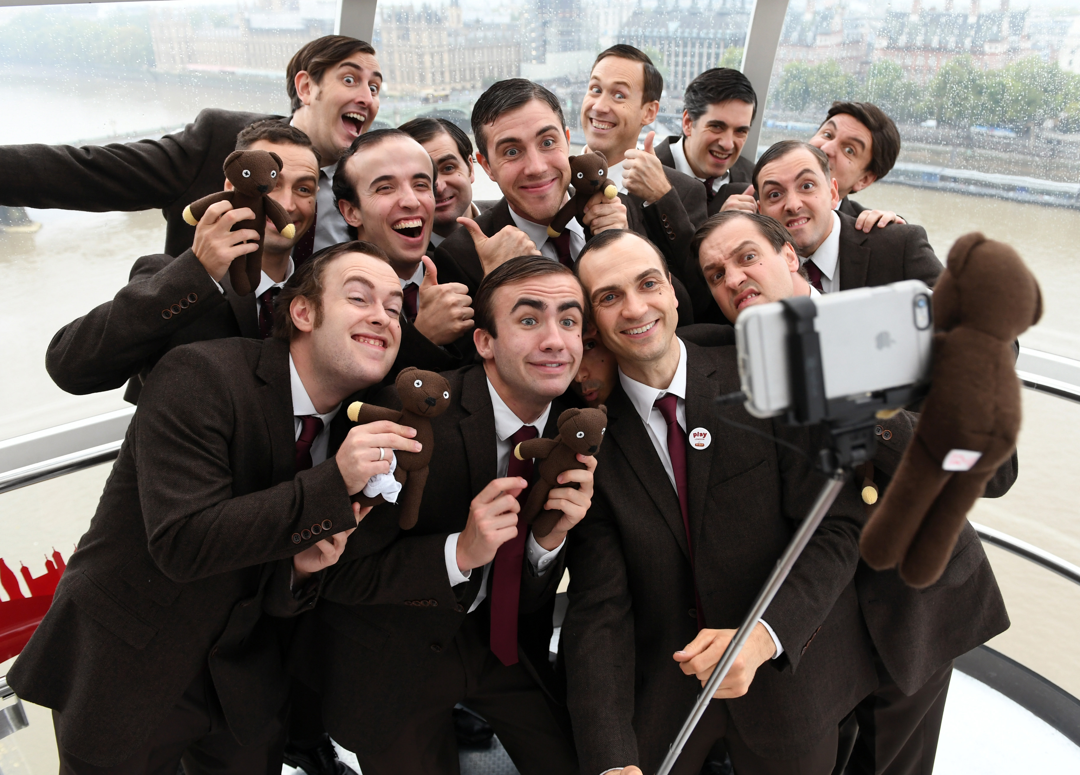 A group of men dressed as Mr Bean pose for a selfie photo in a pod on the London Eye with the Thames in the background
