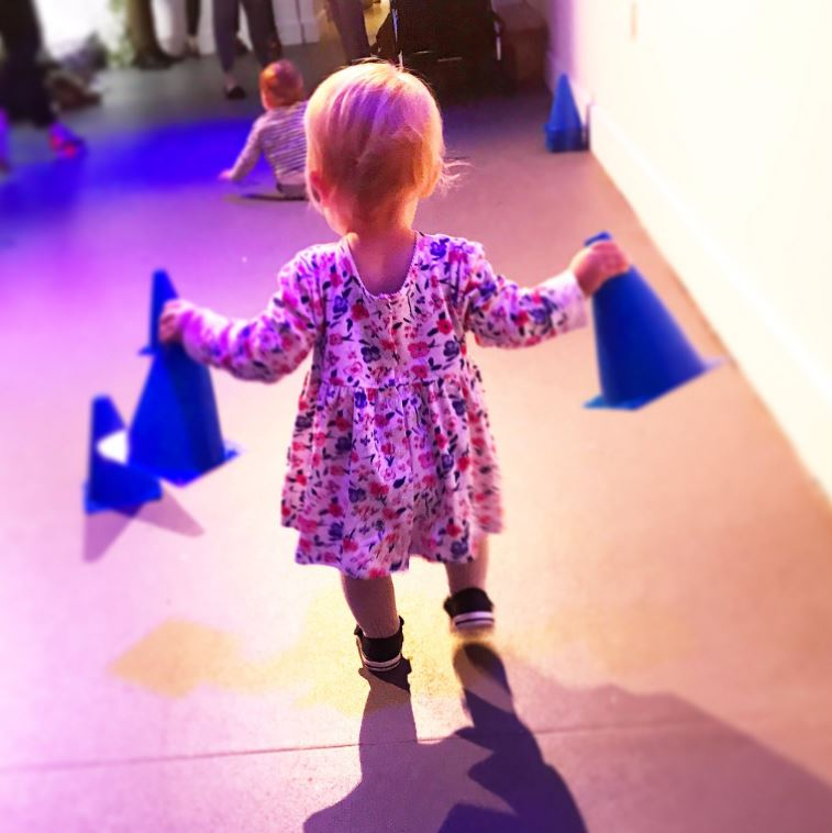 A small child holding the cones from the pushchair slalom challenge